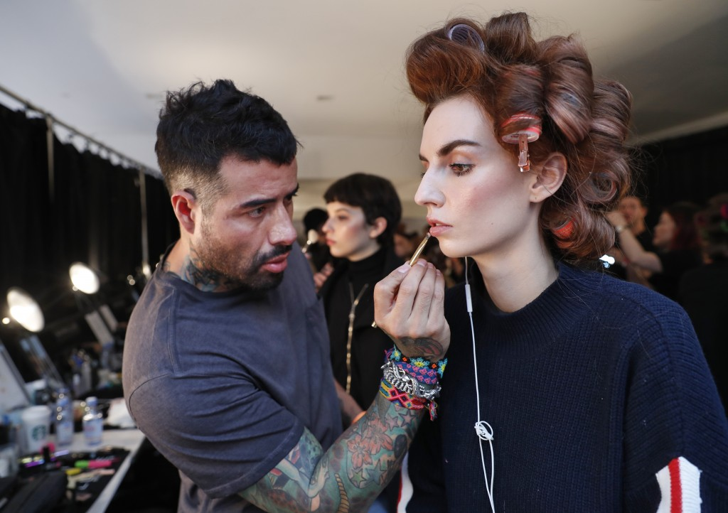 A makeup artist applies makeup to a model's face backstage before the latest fashion creations from Naeem Khan were modeled during New York Fashion We...