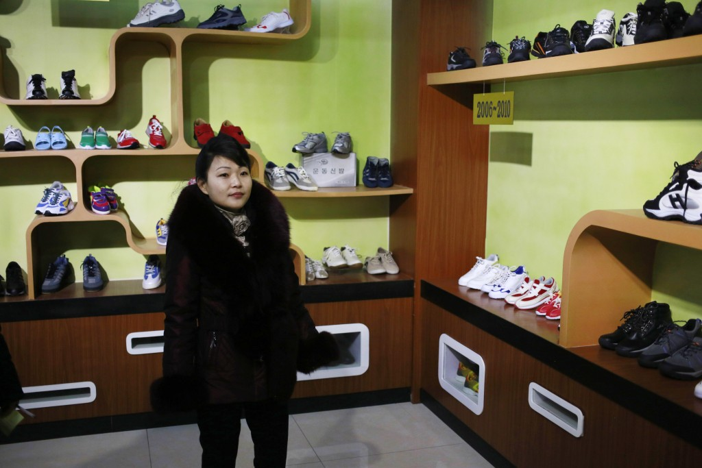 In this Friday, Feb. 1, 2019, photo, a guide stands in a product exhibition room at Ryuwon Shoe Factory that specializes in sports footwear, in Pyongy