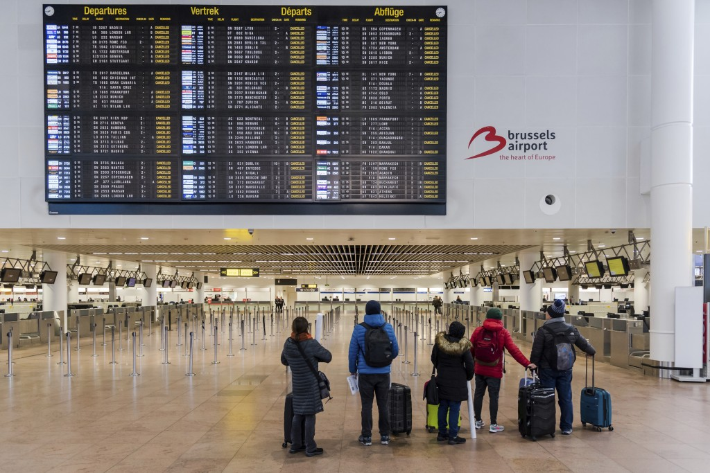 Passengers look at a departure information screen as they stand in a deserted departure hall at the Brussels Airport in Zaventem, Wednesday, Feb. 13, ...