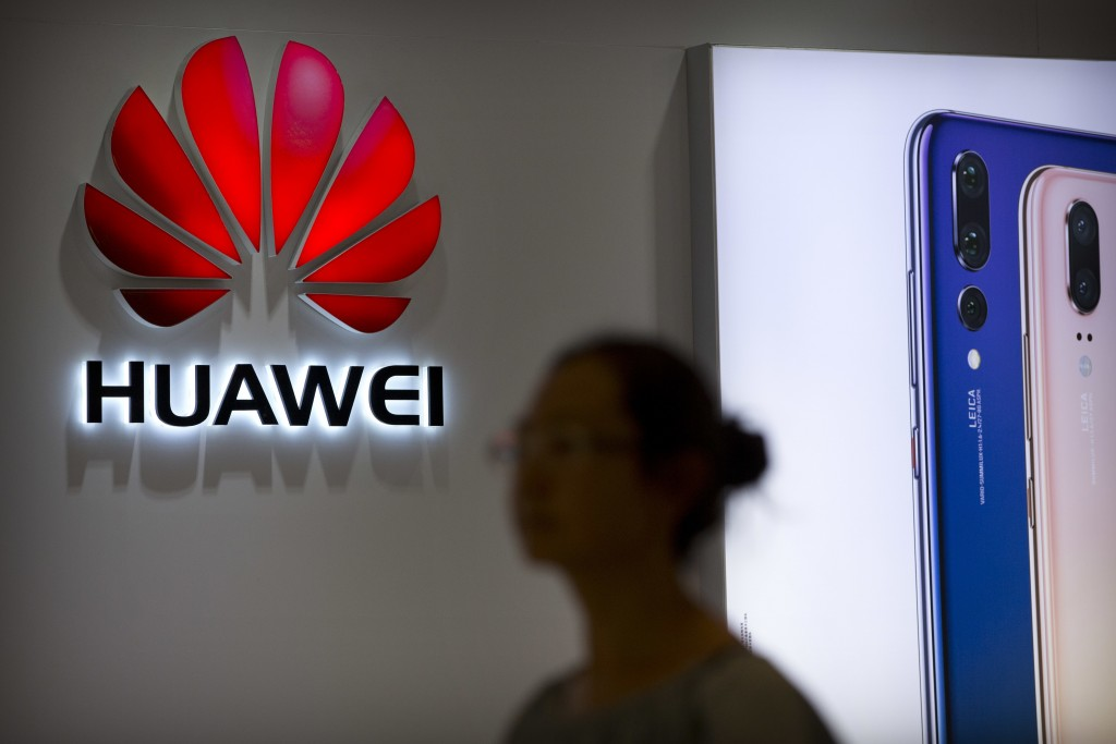 FILE - In this July 4, 2018, file photo, a shopper walks past a Huawei store at a shopping mall in Beijing. Canada's national game _ brought to you by
