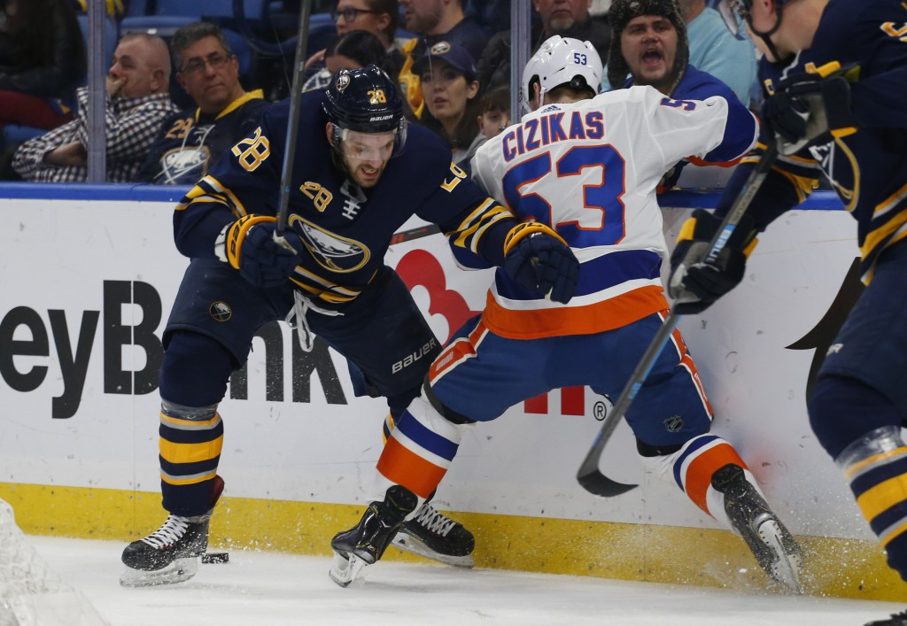 Buffalo Sabres forward Zemgus Girgensons (28) and New York Islanders forward Casey Cizikas (53) battle behind the net during the second period of an N...