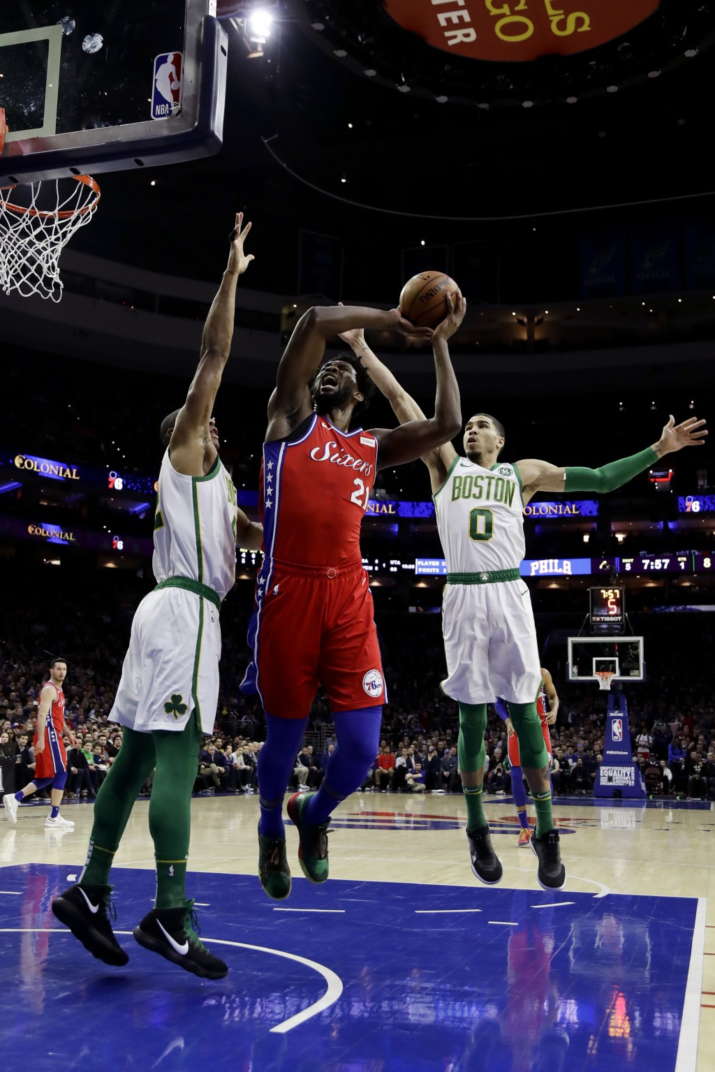 Philadelphia 76ers' Joel Embiid, center, goes up for a shot between Boston Celtics' Al Horford, left, and Jayson Tatum during the first half of an NBA