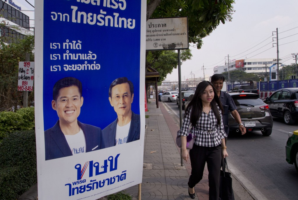 Pedestrians walk past an election poster promoting members of the Thai Raksa Chart political party in Bangkok, Thailand, Wednesday, Feb 13, 2019. The ...