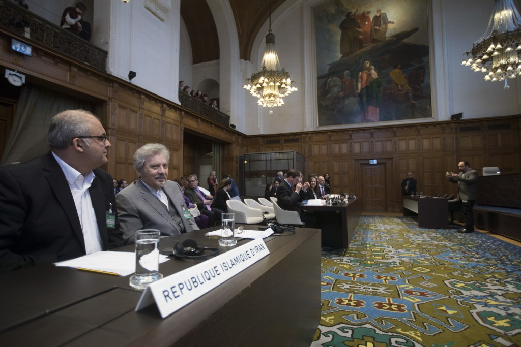 Mohsen Mohebi, agent for the Islamic Republic of Iran, second left, and his delegation take their seats, as the U.S. delegation is seen in the backgro