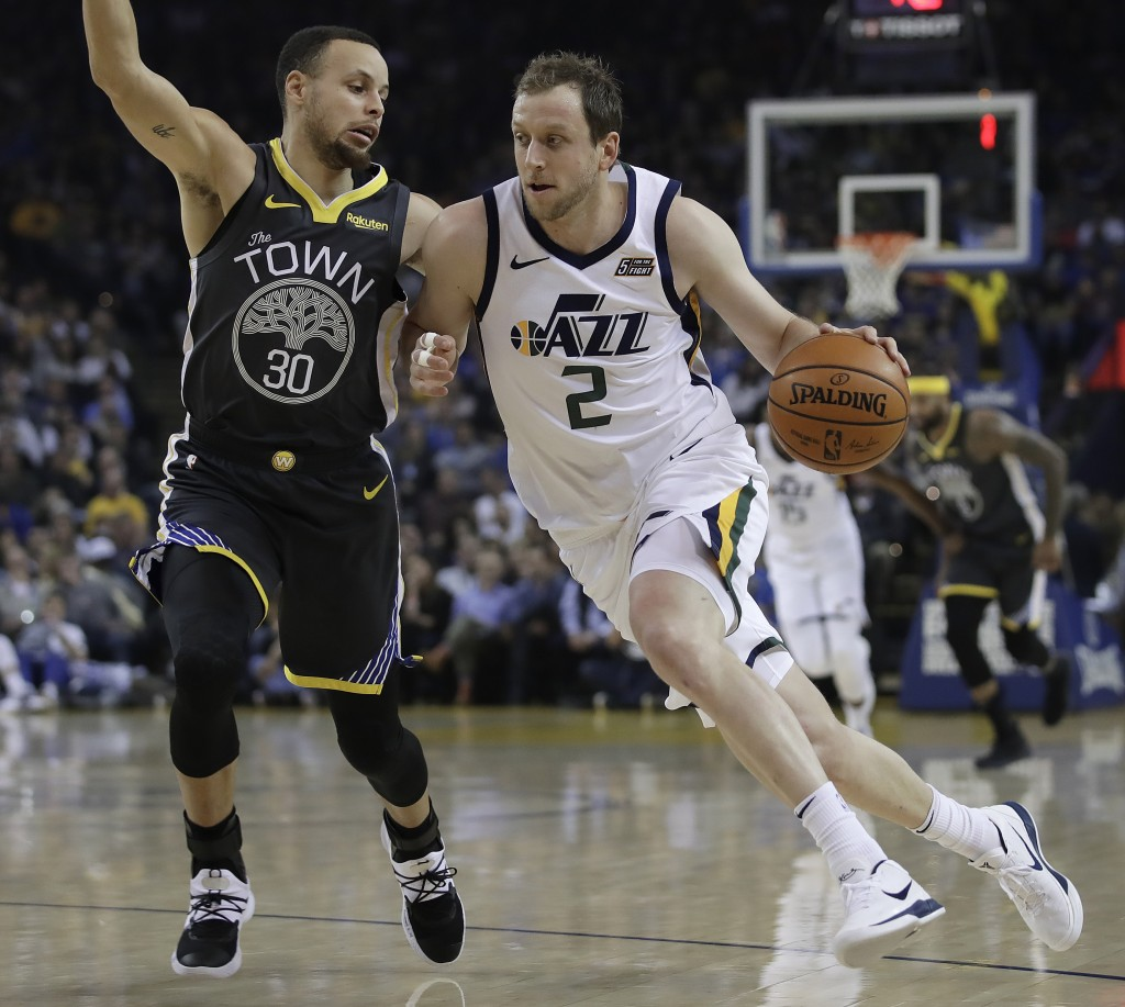 Utah Jazz forward Joe Ingles, right, drives the ball against Golden State Warriors' Stephen Curry (30) during the first half of an NBA basketball game