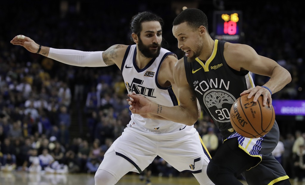 Golden State Warriors' Stephen Curry, right, drives as Utah Jazz guard Ricky Rubio defends during the second half of an NBA basketball game Tuesday, F