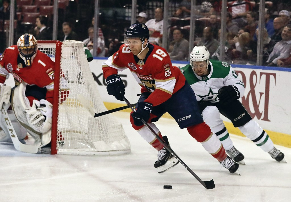 Florida Panthers defenseman Mike Matheson (19) and Dallas Stars center Radek Faksa (12) battle for the puck during the first period of an NHL hockey g...