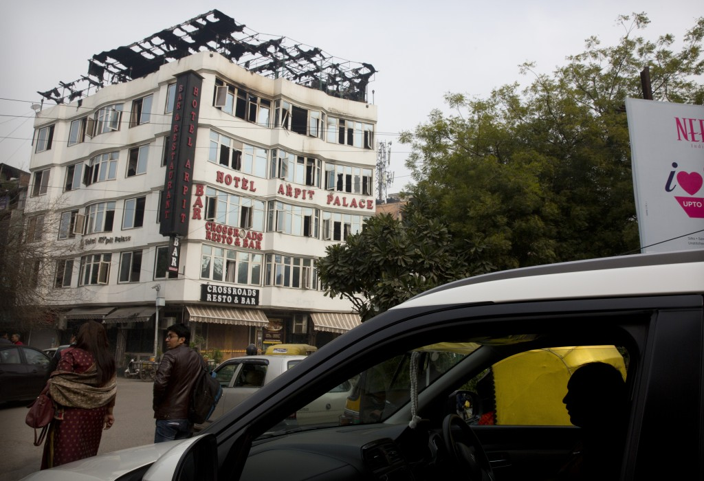 A vehicle drives past Hotel Arpit Palace which caught fire early Tuesday morning in New Delhi, India, Wednesday, Feb. 13, 2019. A fire engulfed the sh