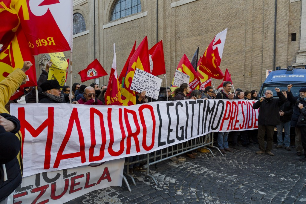 Demonstrators hold banners and placards during a pro-Maduro demonstration in downtown Rome, Tuesday, Feb. 12, 2019. Italian Foreign Minister Enzo Moav