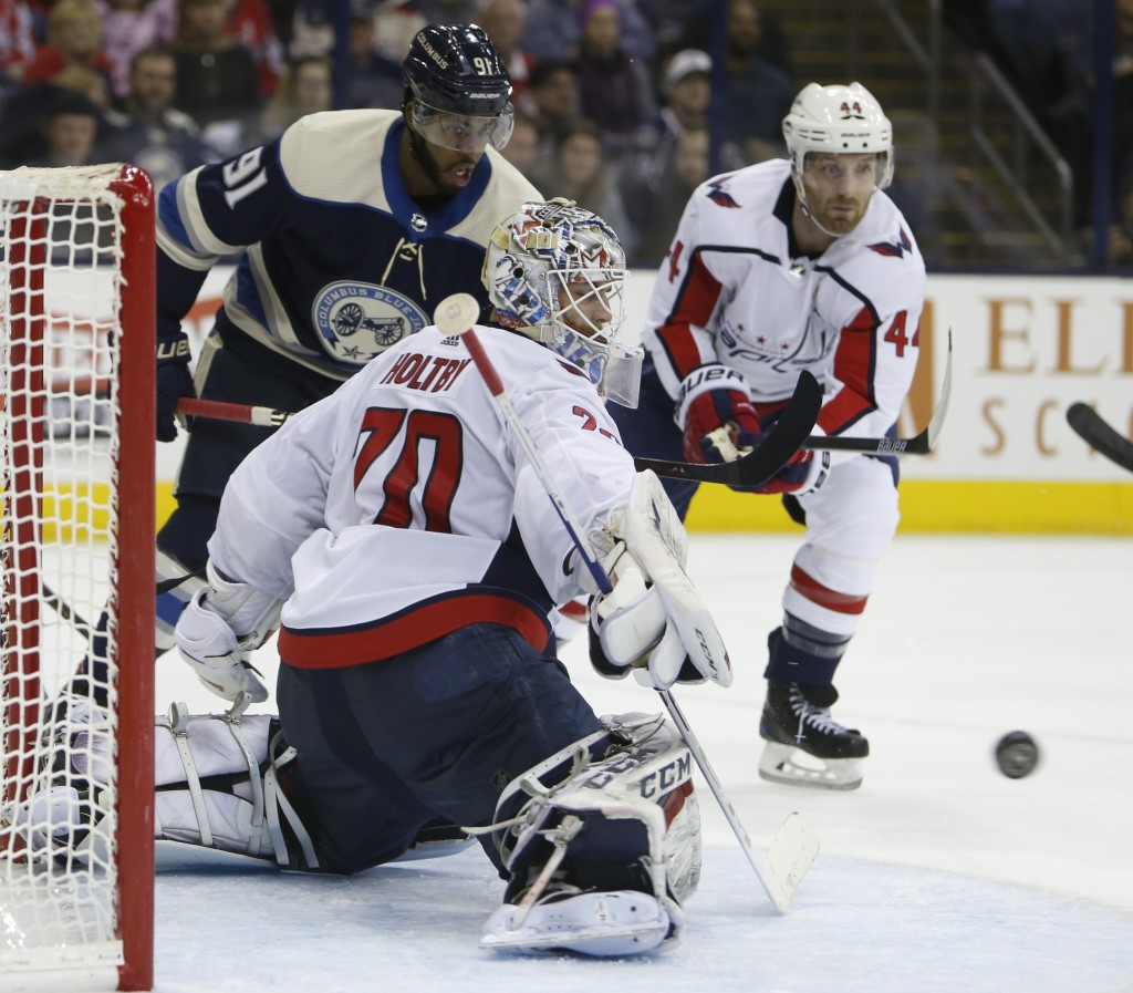Washington Capitals' Braden Holtby, front, makes a save as teammate Brooks Orpik, right, and Columbus Blue Jackets' Anthony Duclair wait for the rebou