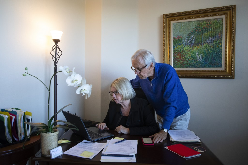 In this Feb. 6, 2019, photo Debbie Douglas works on her computer as her husband and business partner, Gary, watches in their home office in Newport Be...