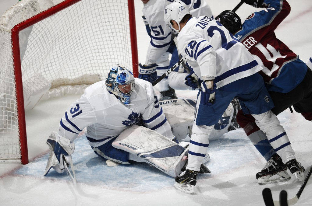 Toronto Maple Leafs goaltender Frederik Andersen, left, sits on the puck after stopping a shot off the stick of Colorado Avalanche left wing A.J. Gree