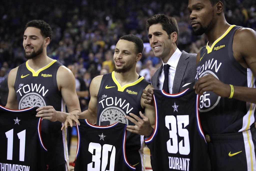 Golden State Warriors general manager Bob Myers, third from left, presents All-Star jerseys to Klay Thompson (11), Stephen Curry (30) and Kevin Durant...