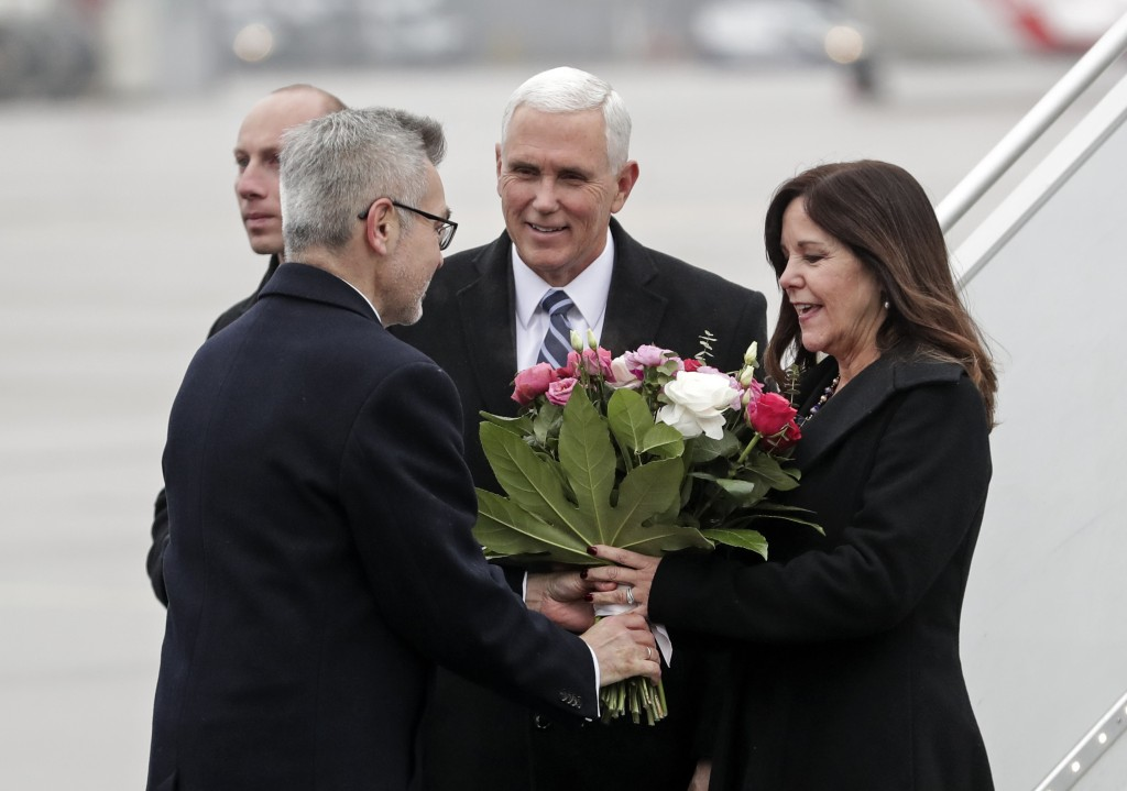 Poland's Minister of Foreign Affairs Jacek Czaputowicz, left, gives flowers to Karen Pence, right, wife of United States Vice President Mike Pence, ce...