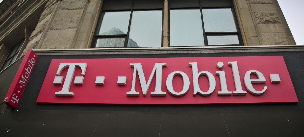 FILE - This April 30, 2018, file photo shows signage a T-Mobile store in New York. The top executives of T-Mobile and Sprint are making the case to Co...