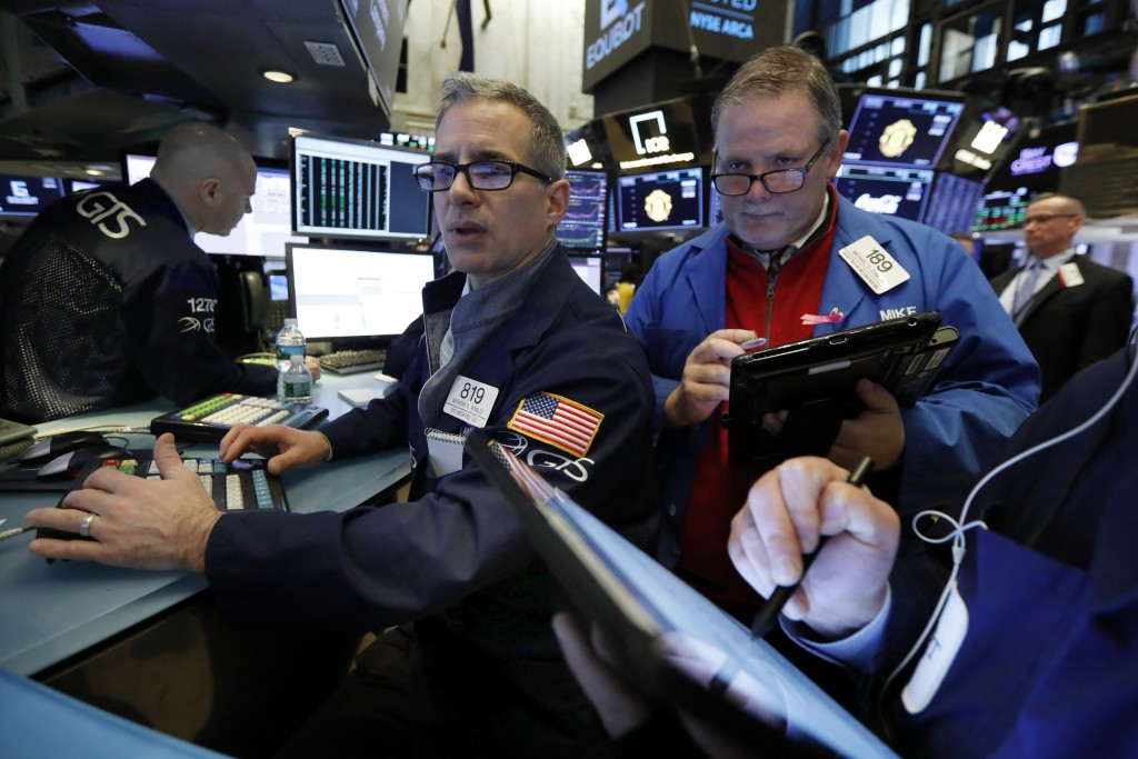 FILE- In this Feb. 5, 2019, file photo specialist Anthony Rinaldi, left, and trader Michael Conlon work on the floor of the New York Stock Exchange. T...
