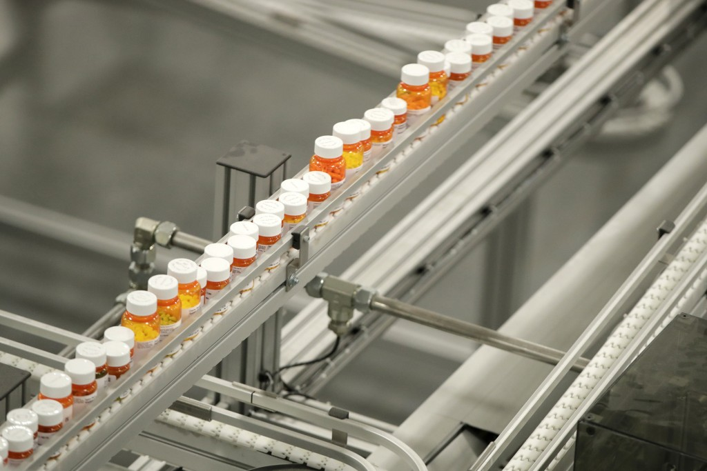 FILE- In this July 10, 2018, file photo bottles of medicine ride on a belt at the Express Scripts mail-in pharmacy warehouse in Florence, N.J. As Demo...