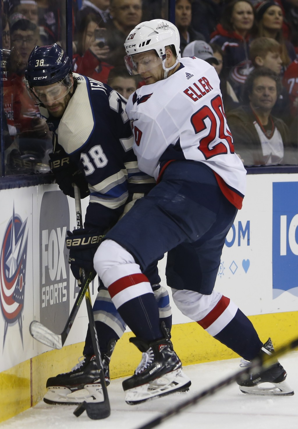 Columbus Blue Jackets' Boone Jenner, left, and Washington Capitals' Lars Eller, of Denmark, right, fight for a loose puck during the first period of a