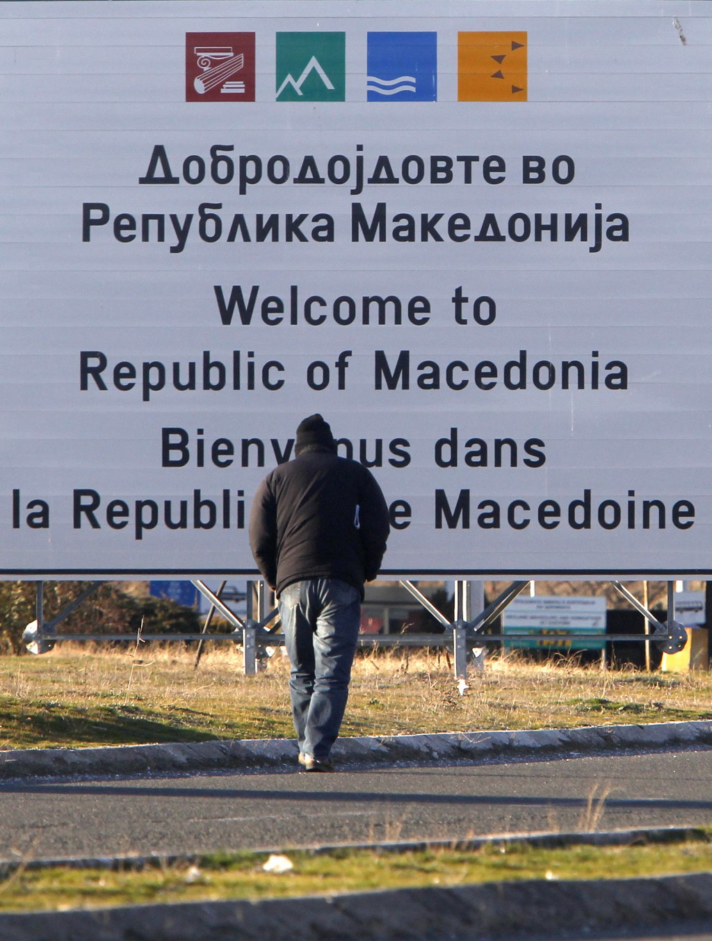 A man walks towards a welcome sign at Bogorodica border crossing, on Macedonia's southern border with Greece, Tuesday, Feb. 12, 2019.  Macedonian auth