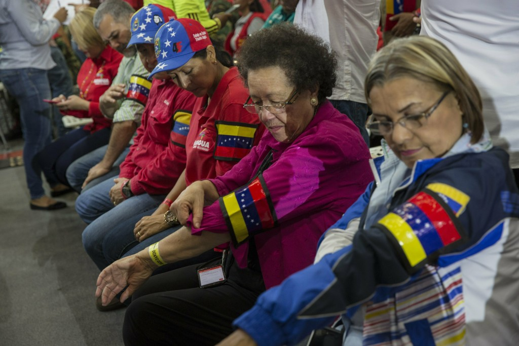 """In this Feb. 6, 2019 photo, guests and government workers place arm bands before the start of  Diosdado Cabello's weekly, live TV program coined: """"Con"""