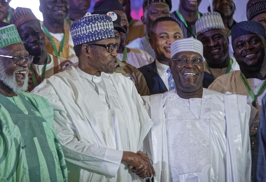 Incumbent President Muhammadu Buhari, left, shakes hands with opposition presidential candidate Atiku Abubakar after signing an electoral peace accord
