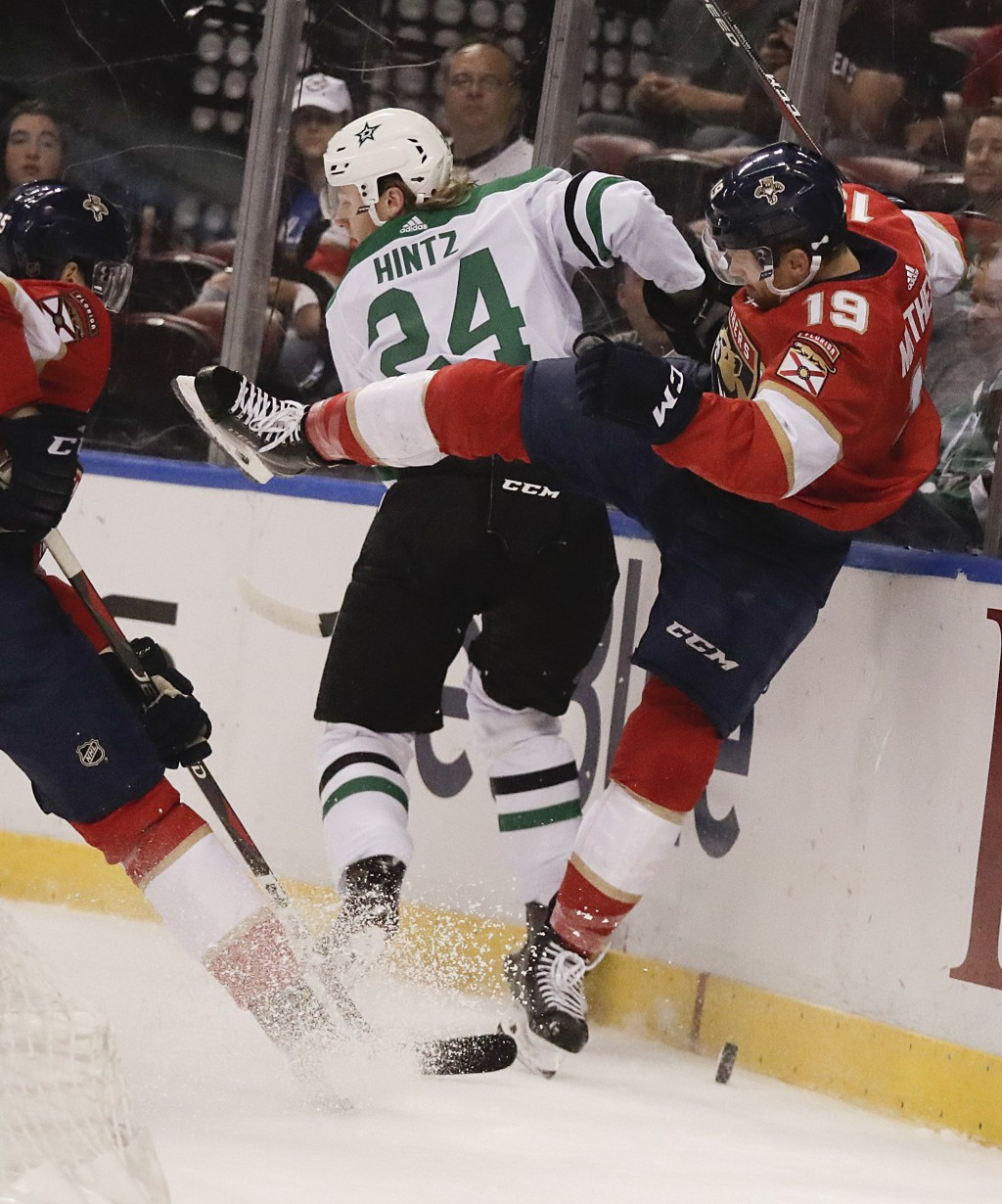 Dallas Stars' Roope Hintz (24) brings Florida Panthers defenseman Mike Matheson (19) to the ice as they battle for the puck during the first period of...