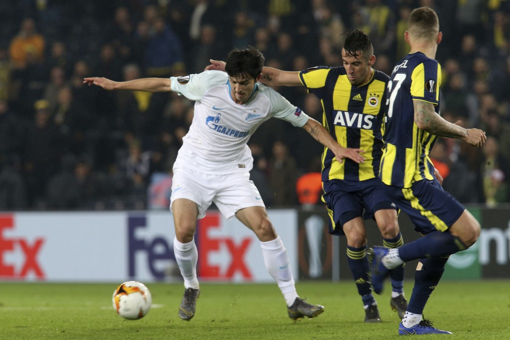 Fenerbahce's Mauricio Isla, center, fights for the ball with Zenit St. Petersburg's Sardar Azmoun during the Europa League round of 32 soccer match be...