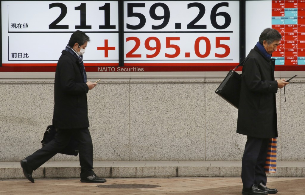 People walk by an electronic stock board of a securities firm in Tokyo, Wednesday, Feb. 13, 2019.  Asian shares were mostly higher Wednesday, cheered