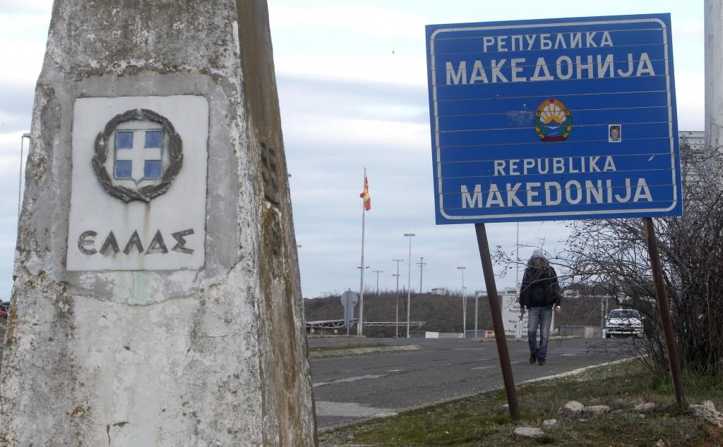 "A man walks next to a road sign reading ""Republic of Macedonia"" and a Greek border stone at Bogorodica border crossing, on Macedonia's southern border..."