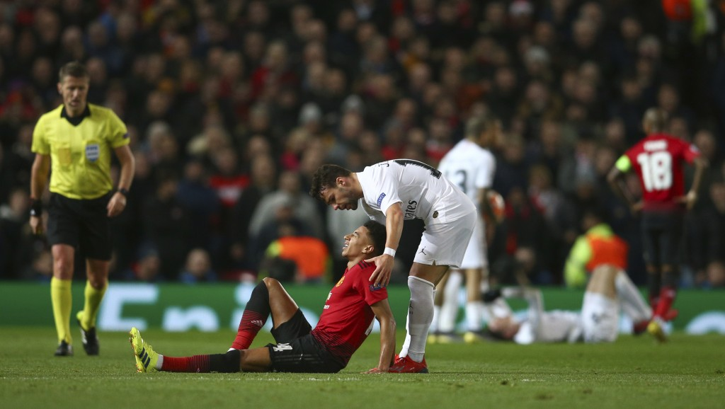 Manchester United's Jesse Lingard, lies injured as Paris Saint Germain's Juan Bernat leans over to help during the Champions League round of 16 soccer...