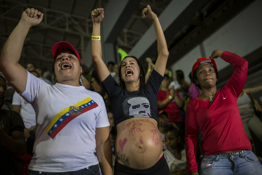 """In this Feb. 6, 2019 photo, Marzuni, whose 8-month pregnant belly carries the Spanish message """"Venezuela is mine,"""" chants pro-government slogans durin"""