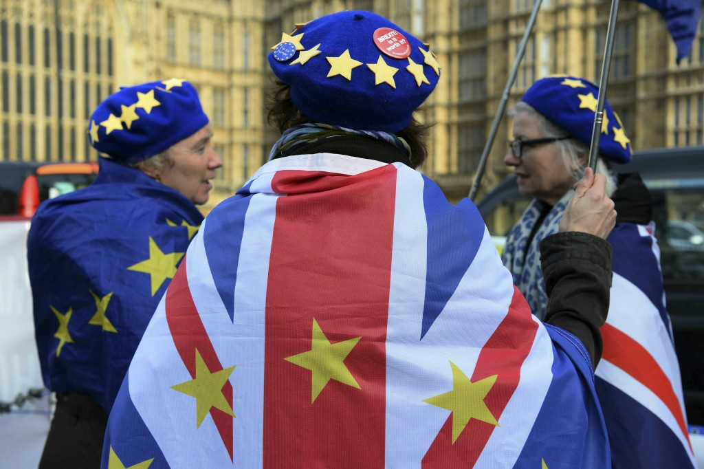 Anti-Brexit protestors wave flags outside Britain's parliament in London, Wednesday Feb. 13, 2019. British Prime Minister Theresa May urged lawmakers ...