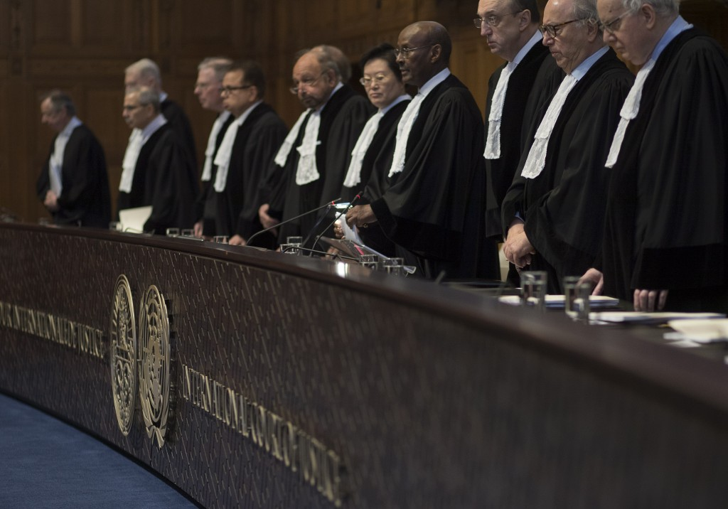 Presiding judge Abdulqawi Ahmed Yusuf of Somalia, fourth from right, and other judges take their seats prior to reading the court's verdict as delegat
