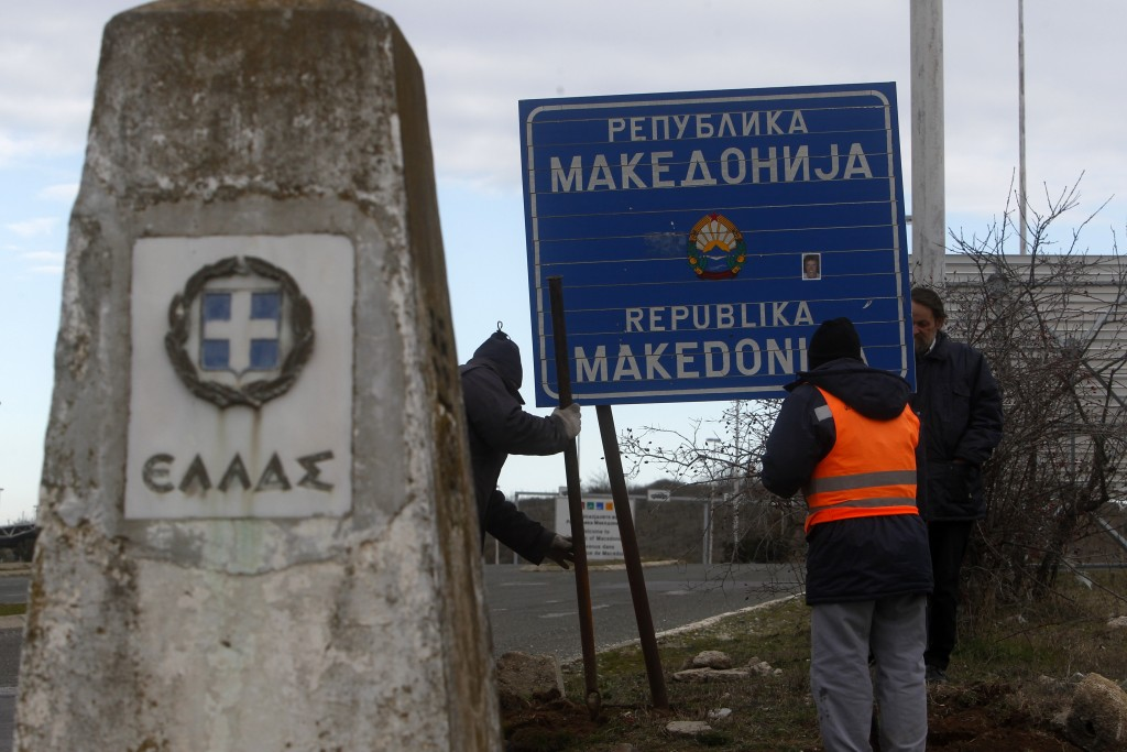 "Workers remove a road sign that reads ''Republic of Macedonia'' as the other sign reads in Greek ""Hellas-Greece"" in the southern border with Greece, n"