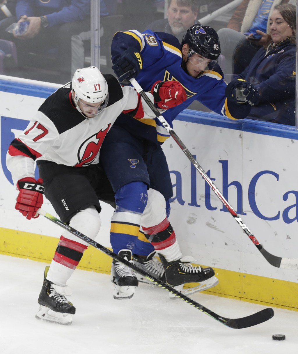 New Jersey Devils' Kenny Agostino (17) battles with St. Louis Blues' Ivan Barbashev (49) along the boards in the third period of an NHL hockey game, T...