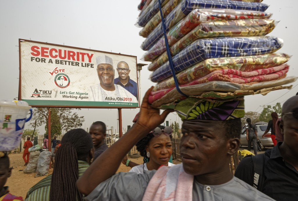 A street seller sells his wares by the side of the road next to a campaign poster for opposition presidential candidate Atiku Abubakar, at a busy inte