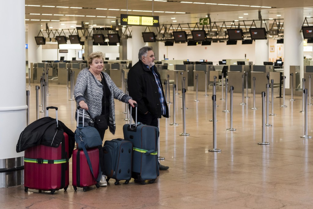 Two passengers wait for information as they stand in a deserted departure hall at Brussels Airport in Zaventem, Wednesday, Feb. 13, 2019. Belgium's ai...