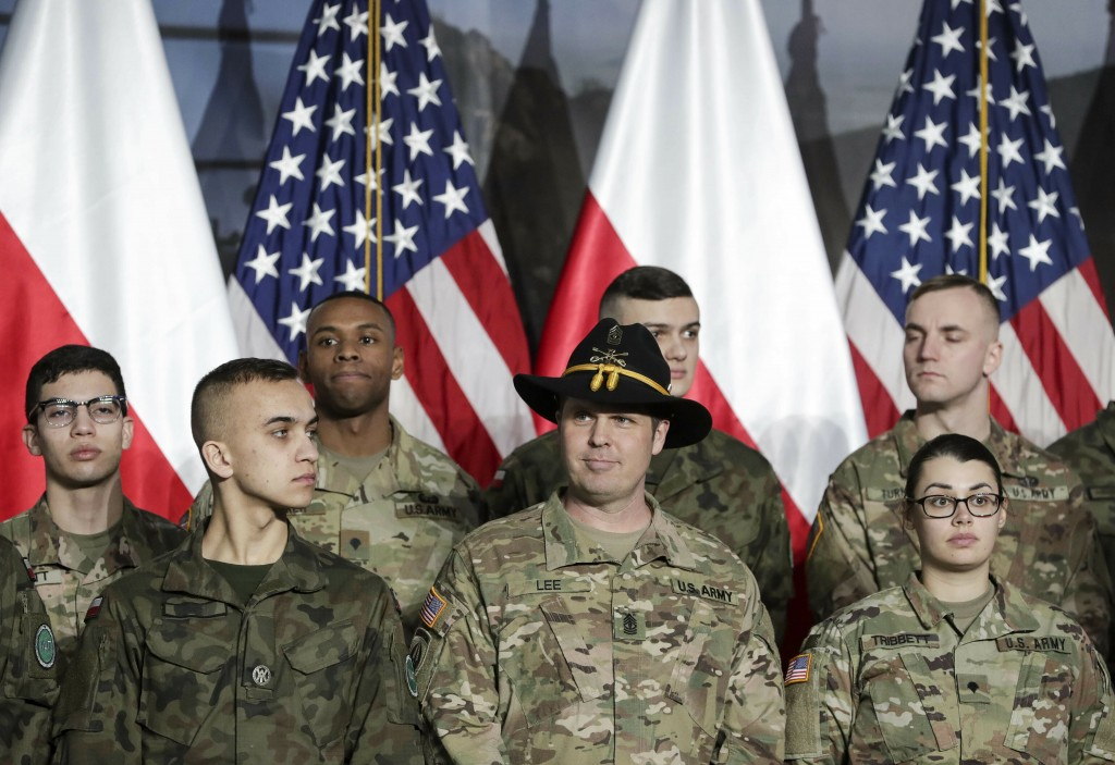 Soldiers from Poland and the United States wait in front of flags for United States Vice President Mike Pence at the airport in Warsaw, Poland, Wednes
