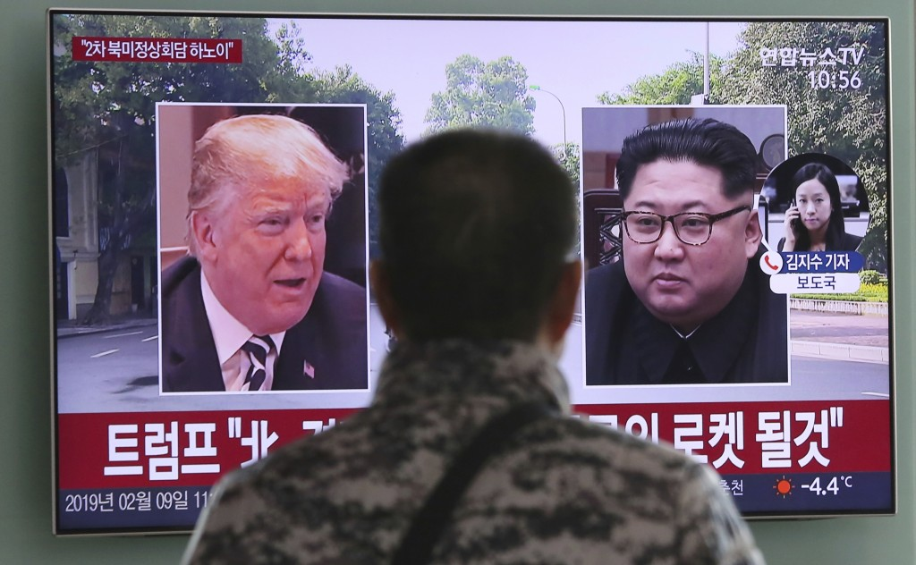 In this Feb. 9, 2019, photo, a man watches a TV screen showing images of U.S. President Donald Trump, left, and North Korean leader Kim Jong Un during...