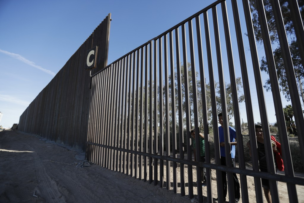 FILE - In this March 5, 2018, file photo, boys look through an older section of the border structure from Mexicali, Mexico, alongside a newly-construc