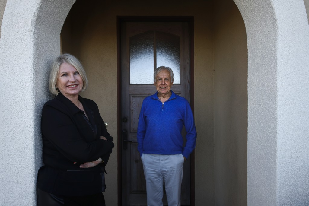In this Feb. 6, 2019, photo Debbie Douglas, left, and her husband and business partner, Gary, pose for a photo in Newport Beach, Calif. In business to