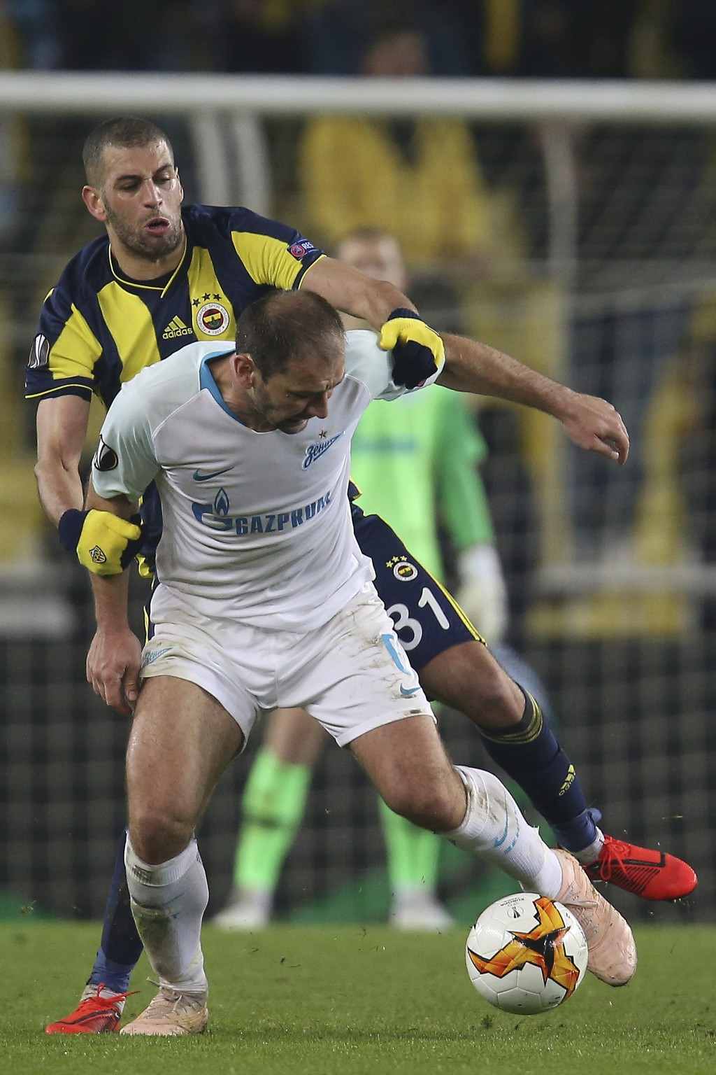 Fenerbahce's Islam Slimani, rear, fights for the ball with Zenit St. Petersburg Branislav Ivanovic during the Europa League round of 32 soccer match b...