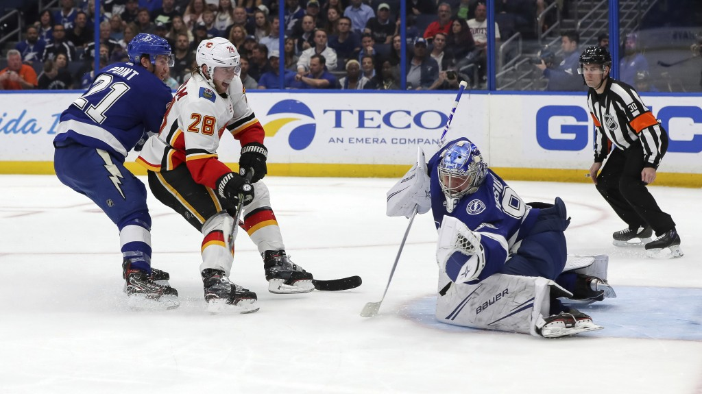 Tampa Bay Lightning goaltender Andrei Vasilevskiy, of Russia, makes a save against Calgary Flames' Elias Lindholm, of Sweden, as Brayden Point (21) de