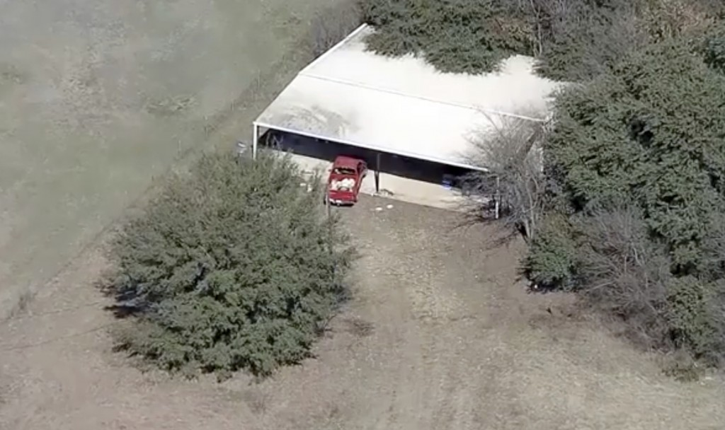 This aerial image provided by KDFW-FOX4 News shows part of the property where deputies found two young, malnourished children locked together in a dog...