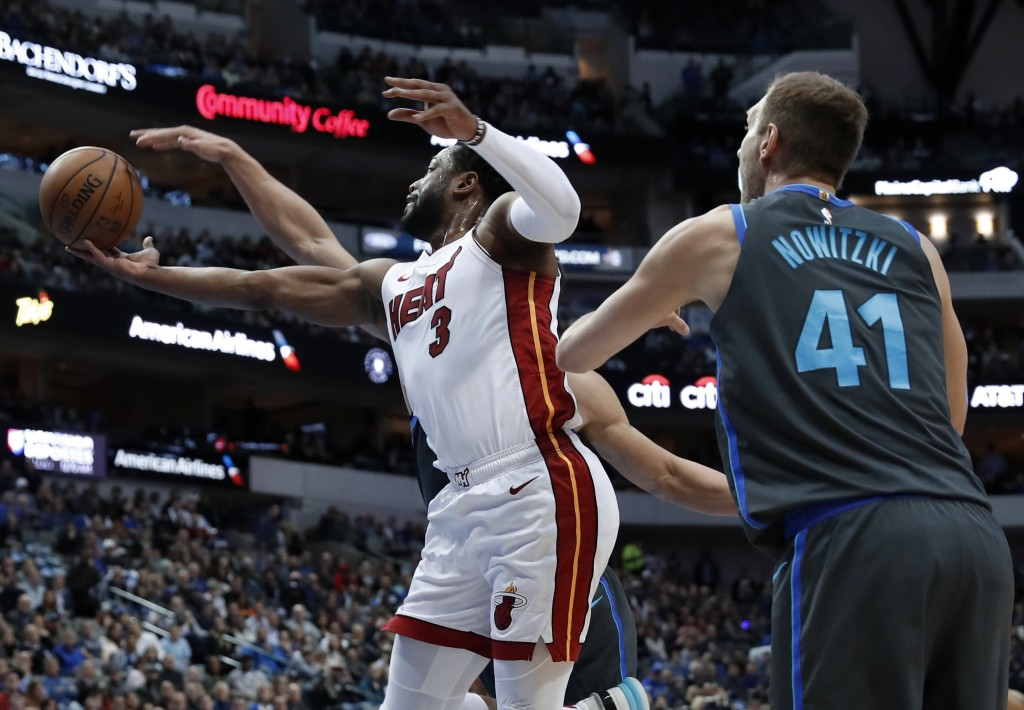 Miami Heat guard Dwyane Wade (3) shoots as Dallas Mavericks' Dirk Nowitzki (41) and Dwight Powell, rear, defend during the first half of an NBA basket