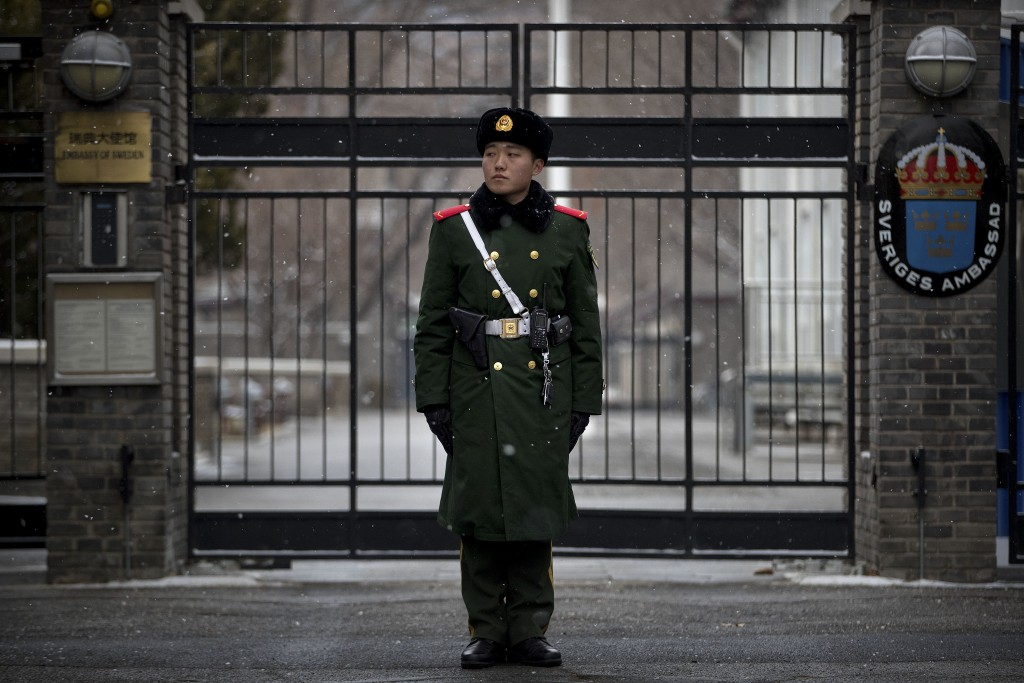 A paramilitary policeman stands guard at the gate of the Swedish Embassy in Beijing, Thursday, Feb. 14, 2019. The embassy said Thursday that Ambassado...