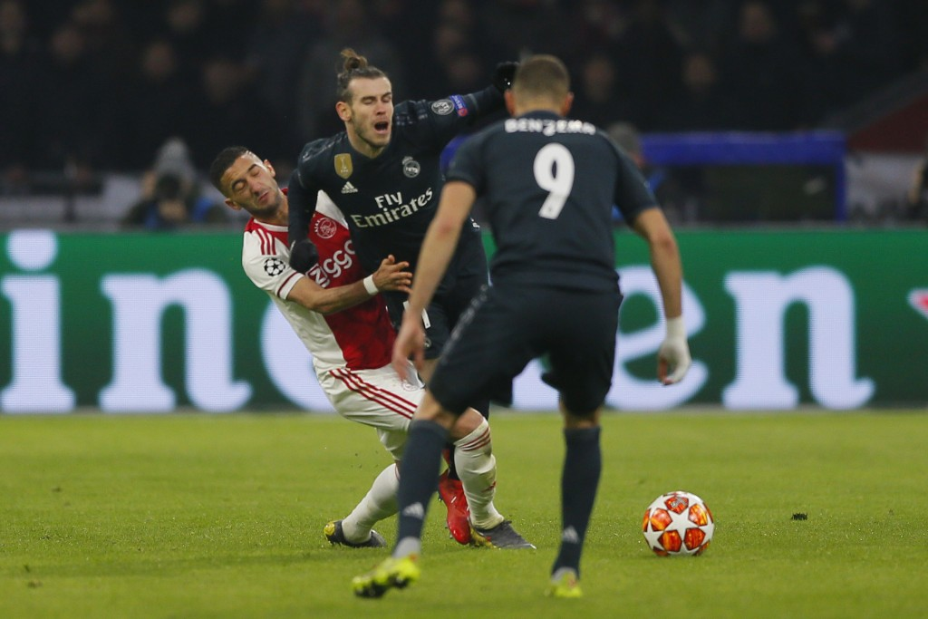 Real midfielder Gareth Bale, center, is tackled by Ajax's Hakim Ziyech, left, during the first leg, round of sixteen, Champions League soccer match be...
