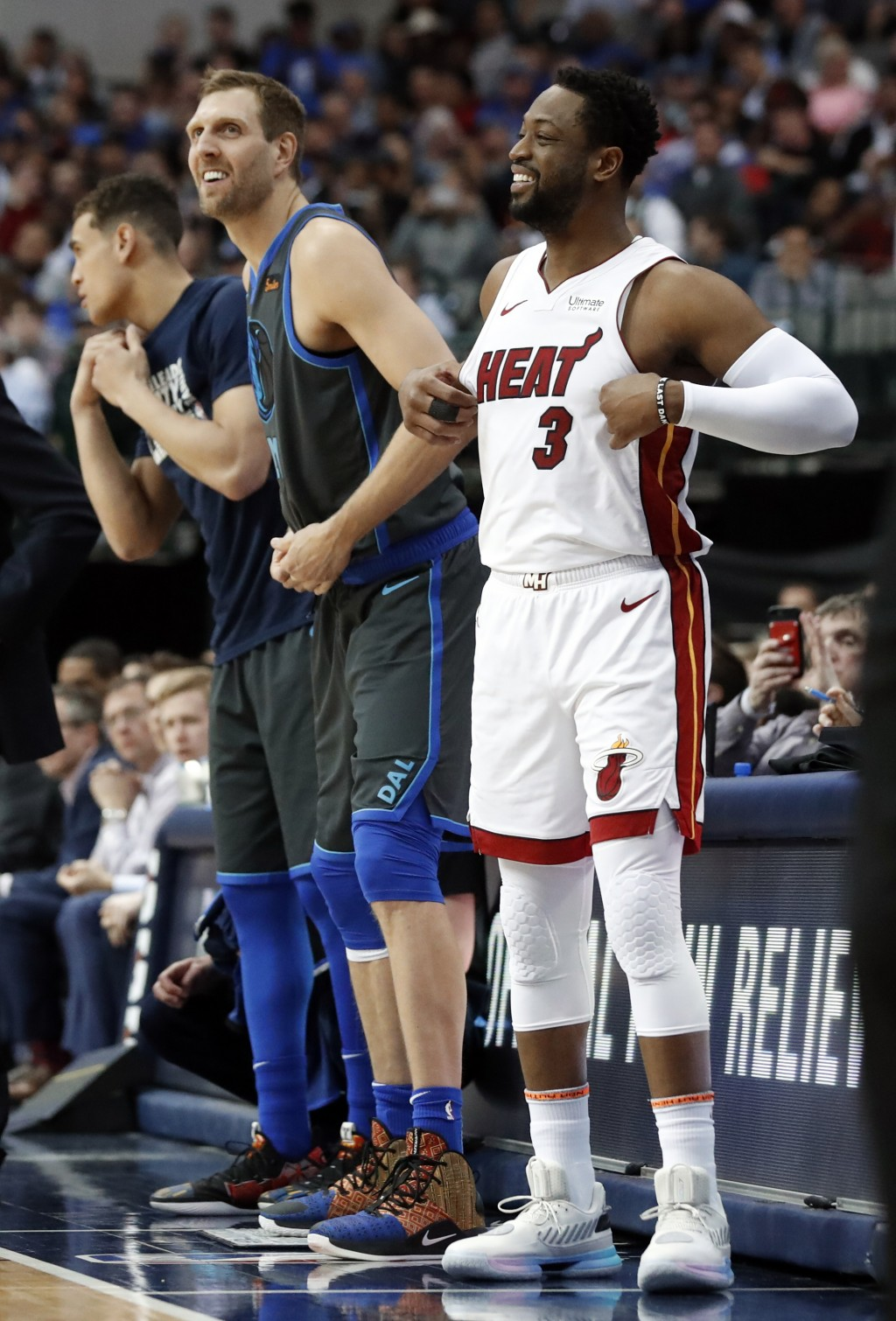 Dallas Mavericks forward Dirk Nowitzki, left, and Miami Heat guard Dwyane Wade, right, prepare to enter during the first half of an NBA basketball gam...