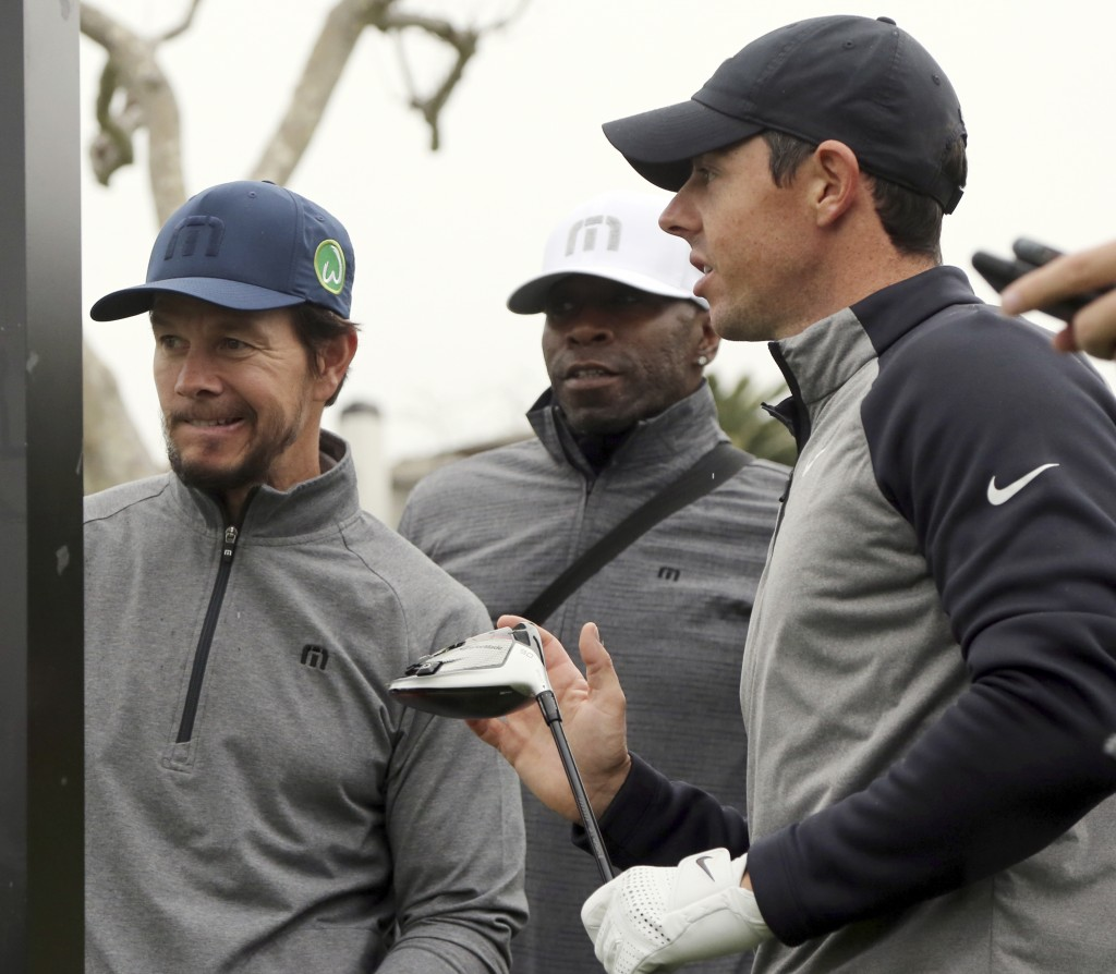 Rory McIlroy, right, and his amateur partner Mark Wahlberg wait on the third tee in the Pro-Am round of the Genesis Open golf tournament at Riviera Co...