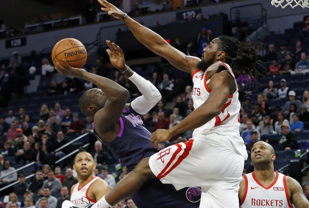 Minnesota Timberwolves' Luol Deng, left, falls back as he shoots while Houston Rockets' Nene tries to block the shot in the first half of an NBA baske